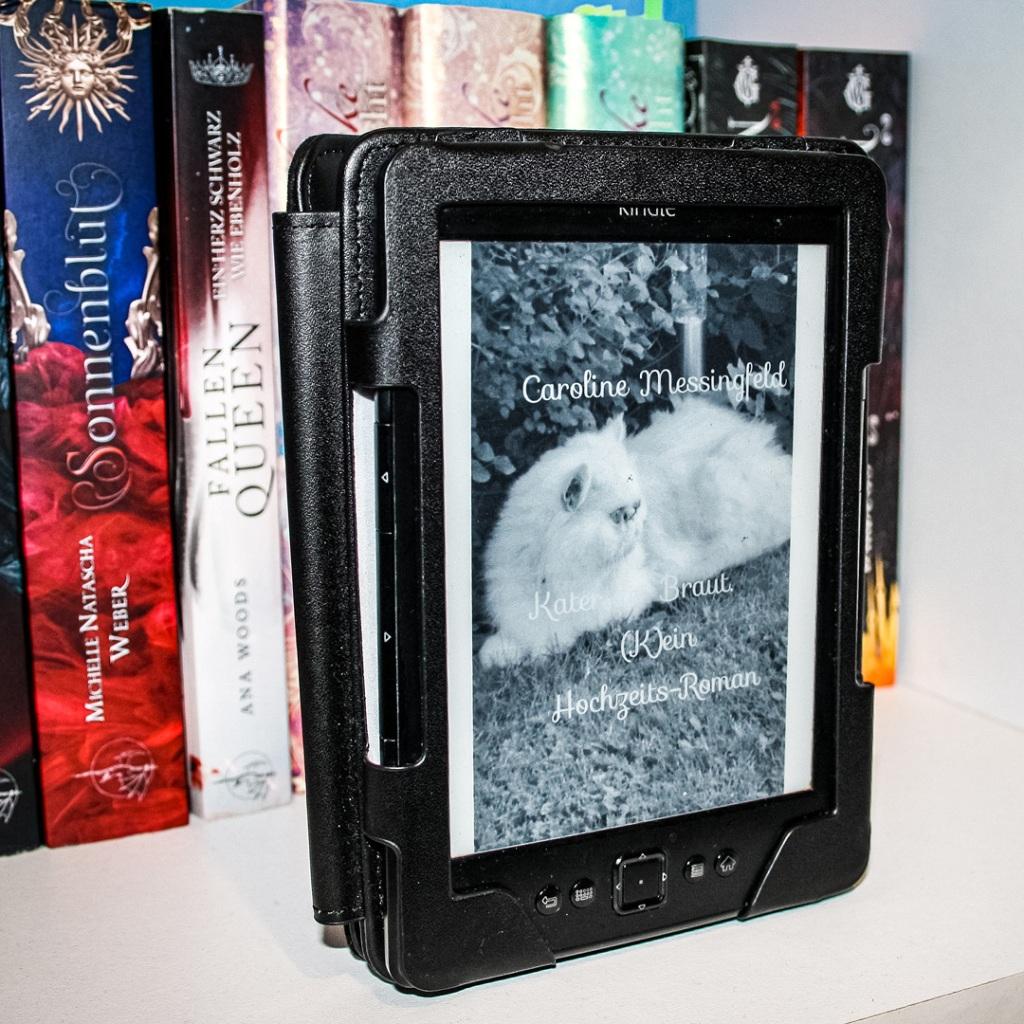 Das Cover von Kater der Braut: eine weiße Perserkatze in einem Garten. Das Cover wird auf einem Kindle abgebildet. Der Kindle steht aufgeklappt in einem Fach eines Bücherregals.